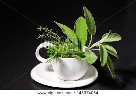 white cup with fresh herbs on black background