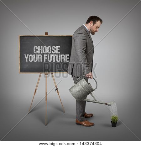 Choose your future text on  blackboard with businessman watering plant