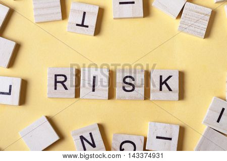 Risk word at wooden blocks on table. Top view.
