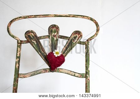 back of a chair vintage iron with a red heart and a daisy,color picture