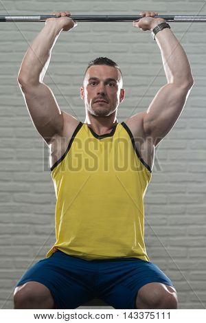 Triceps Exercise With Barbell On White Bricks Background