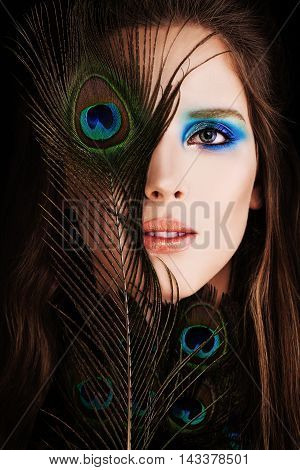 Beautiful Woman. Face with Makeup and Peacock Feather