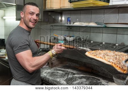 Young Man Putting Pizza Into The Oven