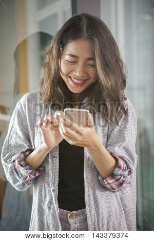 asian younger woman laughing with happiness emotion looking and message chat on smart phone
