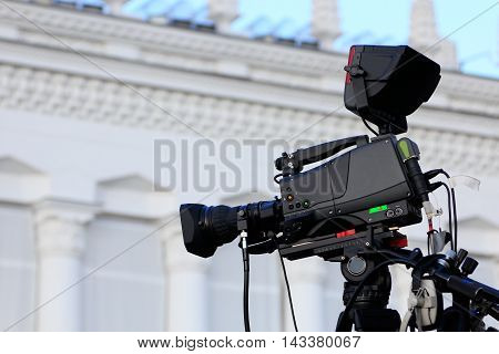 High definition camera on a tripod before live translation of an outdoor event.