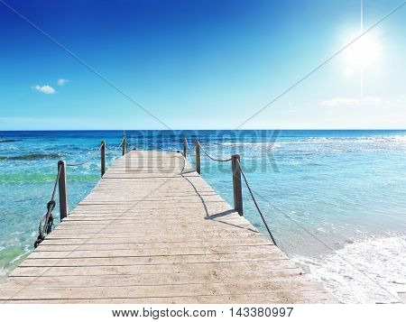 Boardwalk or gangplank into the sea. Wooden pier or jetty and turquoise, wavy sea with bright sun and copy space. Beach background.