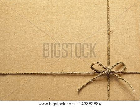 Brown cardboard box tied with a rope