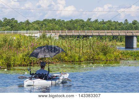 Fisherman in Kayak with umbrella Minocqua Wisconsin