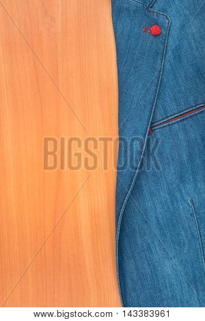 Denim jacket lying on a wooden surface with space for your text