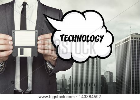Technology text on speech bubble with businessman holding diskette