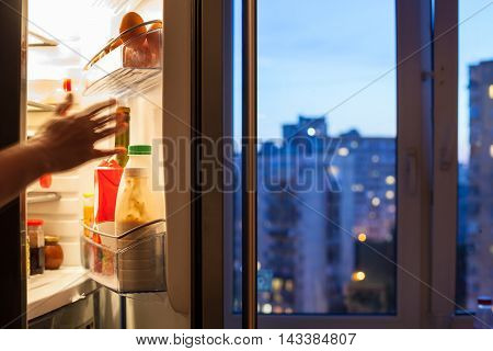 Hand Reaches To Refrigerator And View Of City