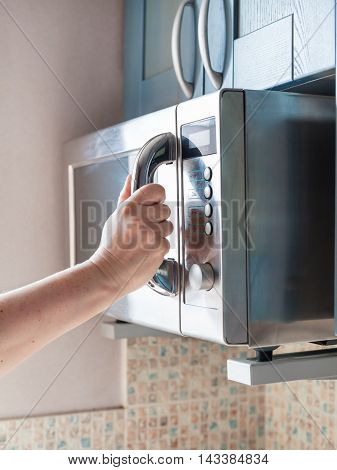 Hand Closes Microwave Oven For Warming Food