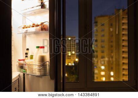 Open Door Of Refrigerator And Urban View In Night