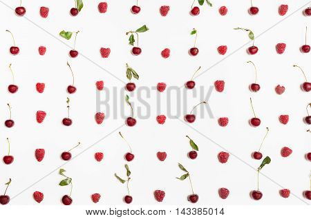 Many Raspberries And Cherries Arranged On White