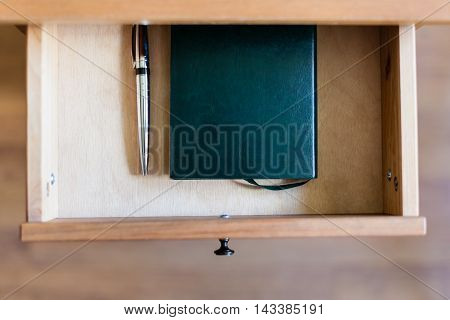 Pen And Notebook In Open Drawer