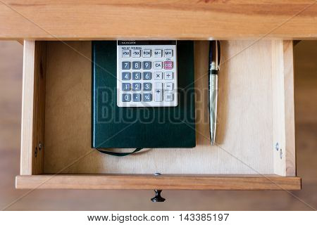Pen, Calculator And Notebook In Open Drawer
