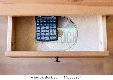 Scientific Calculator And A Cd In Open Drawer