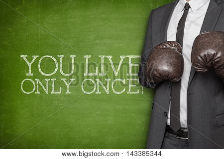 You live only once on blackboard with businessman wearing boxing gloves