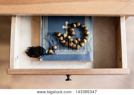 Rosary On Bible Book In Open Drawer