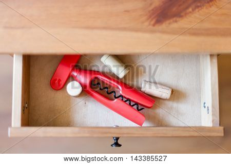 Corkscrew And Cork From Bottles In Open Drawer
