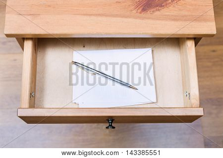 Folded Note And Pen In Open Drawer