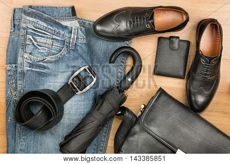 Classic black shoes briefcase jeans and umbrella on the wooden floor can be used as background