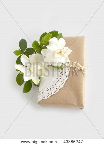 Gift box with beautiful white gardenia flower on white background