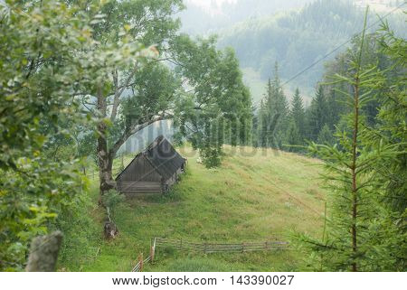 Old rural hut in the Carpathian Mountains. In the background the mountains in the haze