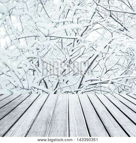 Abstract Christmas table background - Beautiful wood board table in front of Christmas tree branches with white snow
