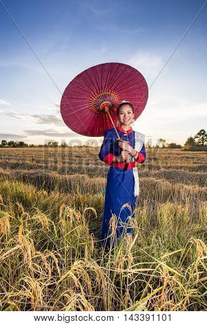 Woman performing typical thai dance on sunset