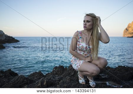 blonde dressed in floral dress in a cove on the island of Mallorca next to the Mediterranean Sea