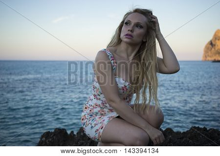 summer blonde dressed in floral dress in a cove on the island of Mallorca next to the Mediterranean Sea