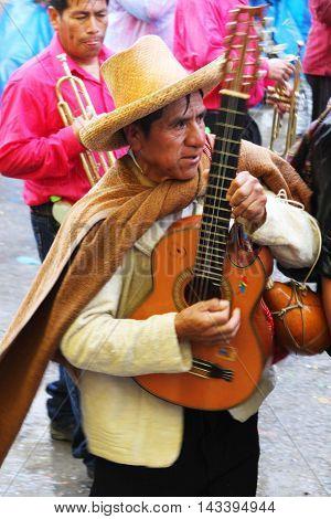 Cajamarca Peru - February 8 2016: Andean man with sombrero plays guitar in Carnival parade in Cajamarca Peru on February 8 2016