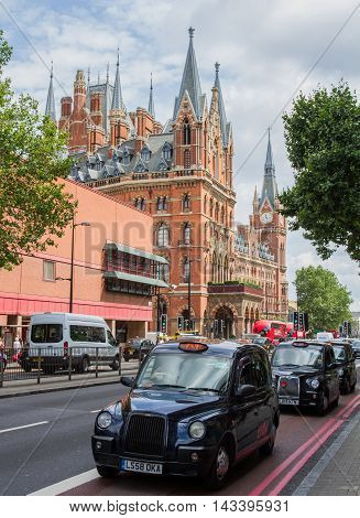 KING'S CROSS, LONDON, UK - JULY 21, 2016. Black London taxis queueing on the Euston Road with the Gothic architecture of St Pancras International train station in the background.
