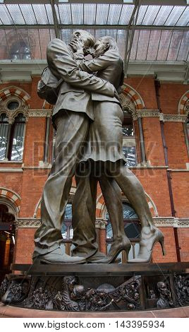 ST PANCRAS, LONDON, UK - JULY 21, 2016. The statue of an embracing couple known as The Meeting Place by the artist Paul Day greets rail passengers on their arrival at St Pancras International Train Station in London.
