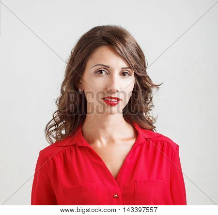 Beautiful Young Girl In A Red Blouse Smiles On White Background