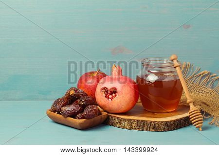 Honey pomegranate apple and dates on wooden board. Jewish New Year Rosh hashana celebration