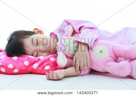Healthy children concept. Closeup of asian child sleeping peacefully. Adorable girl in pink pajamas sleep tight on bed in the bedroom at night on white background.