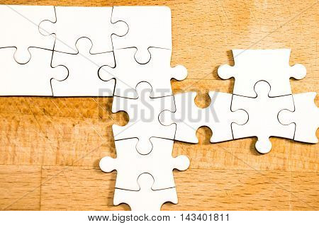 white jigsaw/puzzle over a wooden table background symbol of problem solving