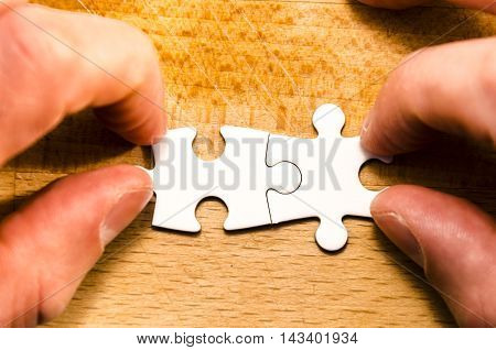 first two pieces of white jigsaw/puzzle over a wooden table background symbol of problem solving