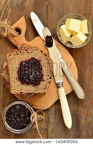 Wholegrain toast with blackcurrant jam and butter, top view, vertical
