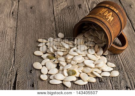 Pumpkin seeds in a brown wooden mug on a gray table.