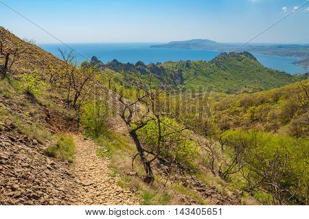 Spring landscape with hiking path on Karadag volcanic mountain range in Eastern Crimea on a Black Sea shore