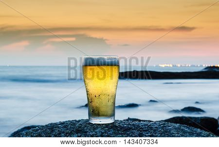 a glass of beer with sea background