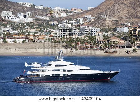 The view of a luxury boat with Cabo San Lucas resort town in a background (Mexico).