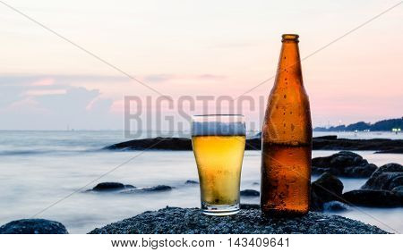 Glass of beer with sea background, Thailand