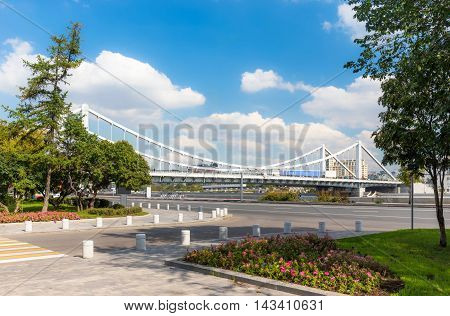 Krymsky Bridge in Moscow Russia with plants on a foreground. View from Frunzenskaya embankment.