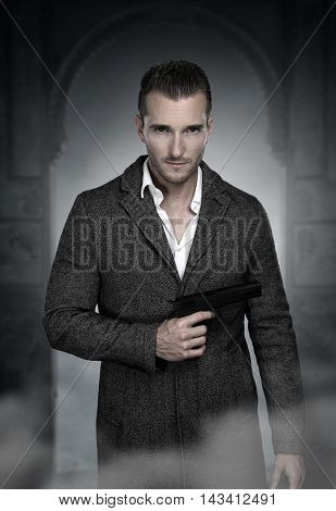 handsome man wearing a long jacket holding a gun