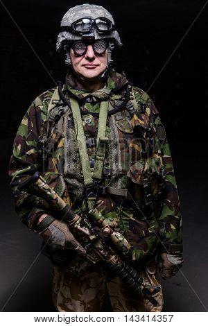 Soldier in helmet weird glasses with rifle on dark background