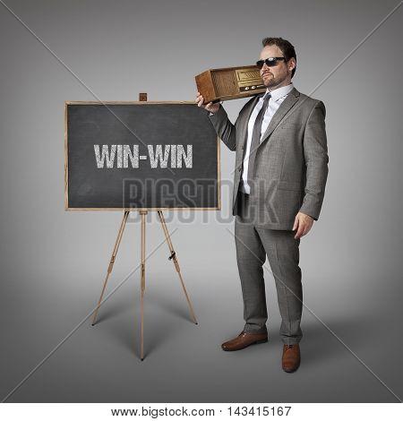 Win-Win text on blackboard with businessman holding radio